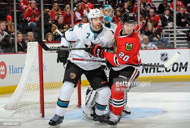 Brad Stuart of the San Jose Sharks and Brandon Saad of the Chicago Blackhawks battle for position in front of goalie Alex Stalock of the Sharks...