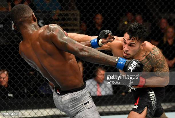 Brad Tavares punches Israel Adesanya of Nigeria in their middleweight bout during The Ultimate Fighter Finale event inside The Pearl concert theater...
