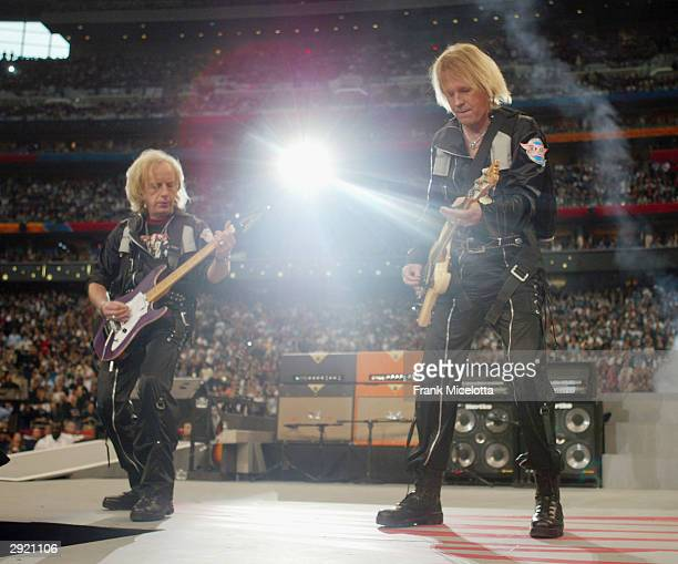 Brad Whitford and Tom Hamilton of Aerosmith perform at the pre-game show prior to the start of Super Bowl XXXVIII between the New England Patriots...