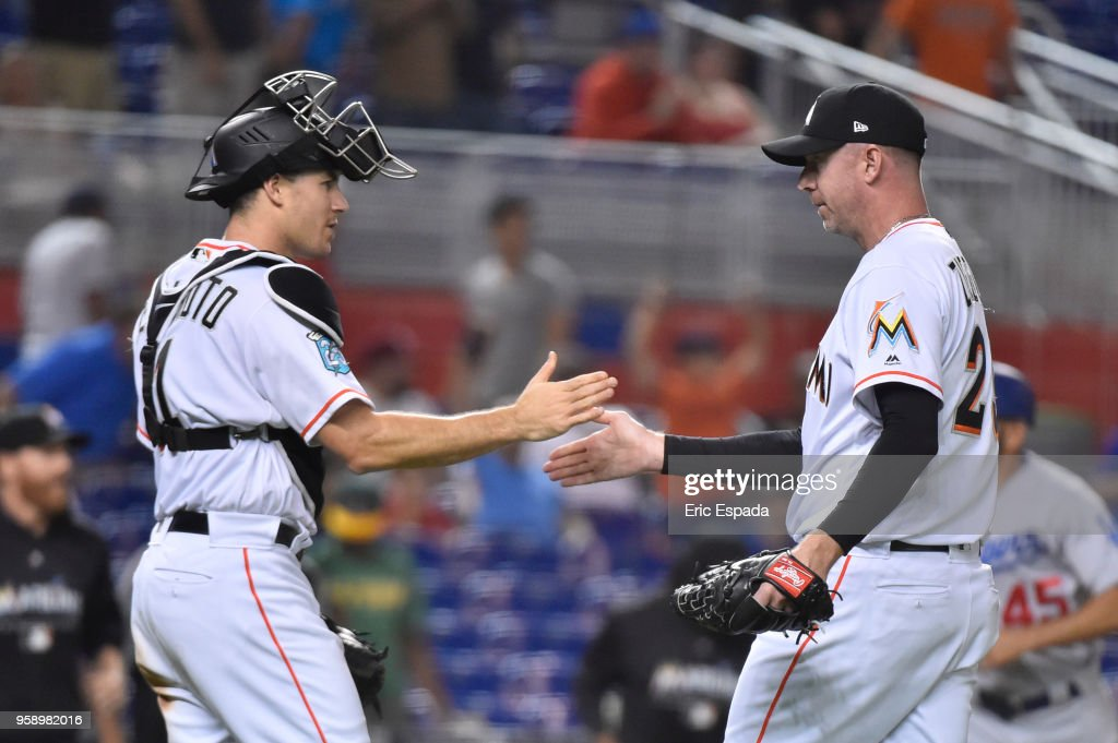 Brad Ziegler #29 of the Miami Marlins shakes hands with J.T. Realmuto #11 after defeating the Los Angeles Dodgers at Marlins Park on May 15, 2018 in Miami, Florida.