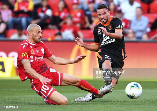 Bradden Inman of the Brisbane Roar shoots for goal defended by James Troisi of Adelaide United during the Round 5 A-League match between Adelaide...