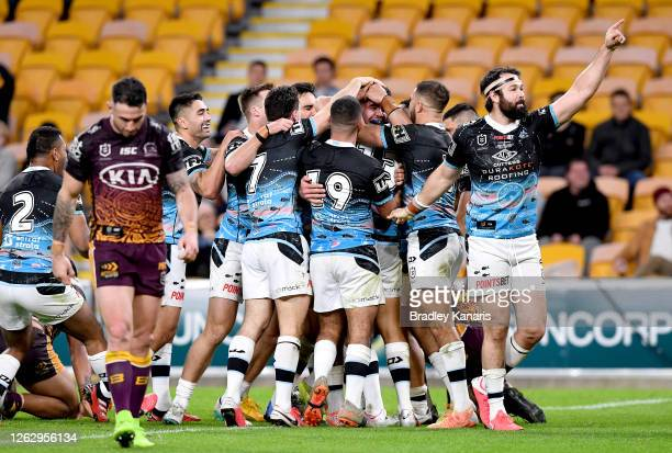Braden Hamlin-Uele of the Sharks is congratulated by team mates after scoring a try during the round 12 NRL match between the Brisbane Broncos and...
