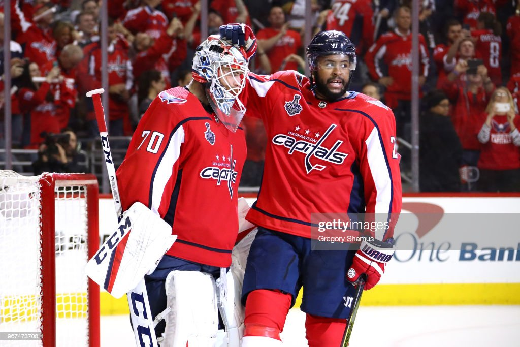 Braden Holtby #70 and Devante Smith-Pelly #25 of the Washington Capitals celebrate their team's 6-2 win over the Vegas Golden Knights in Game Four of the 2018 NHL Stanley Cup Final at Capital One Arena on June 4, 2018 in Washington, DC.