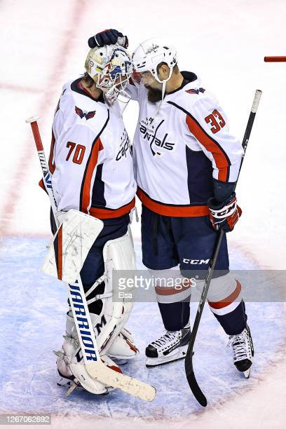 Braden Holtby and Radko Gudas of the Washington Capitals celebrate their teams 32 win against the New York Islanders in Game Four of the Eastern...