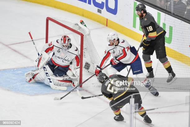 Braden Holtby makes a save while his teammate John Carlson of the Washington Capitals defends against Erik Haula and James Neal of the Vegas Golden...
