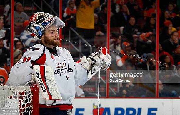 Braden Holtby of the Washington Capitals expels water during a break in the second period against the Philadelphia Flyers at the Wells Fargo Center...