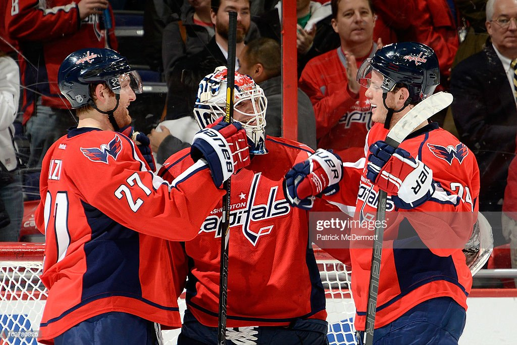 Braden Holtby #70 of the Washington Capitals is congratulated by Karl Alzner (left) and John Carlson (right) after shutting out the Carolina Hurricanes at Verizon Center on February 26, 2013 in Washington, DC.