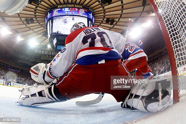 Braden Holtby of the Washington Capitals makes a glove save against Chris Kreider of the New York Rangers during Game Five of the Eastern Conference...
