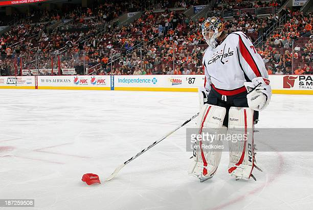 Braden Holtby of the Washington Capitals pushes a hat off the ice that was thrown for Joel Ward's hat trick against the Philadelphia Flyers on...