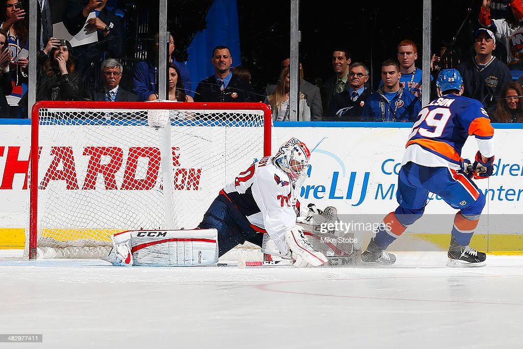 Braden Holtby #70 of the Washington Capitals stops Brock Nelson #29 of the New York Islanders in the shootout at Nassau Veterans Memorial Coliseum on April 5, 2014 in Uniondale, New York. The Capitals defeated the Islanders 4-3.