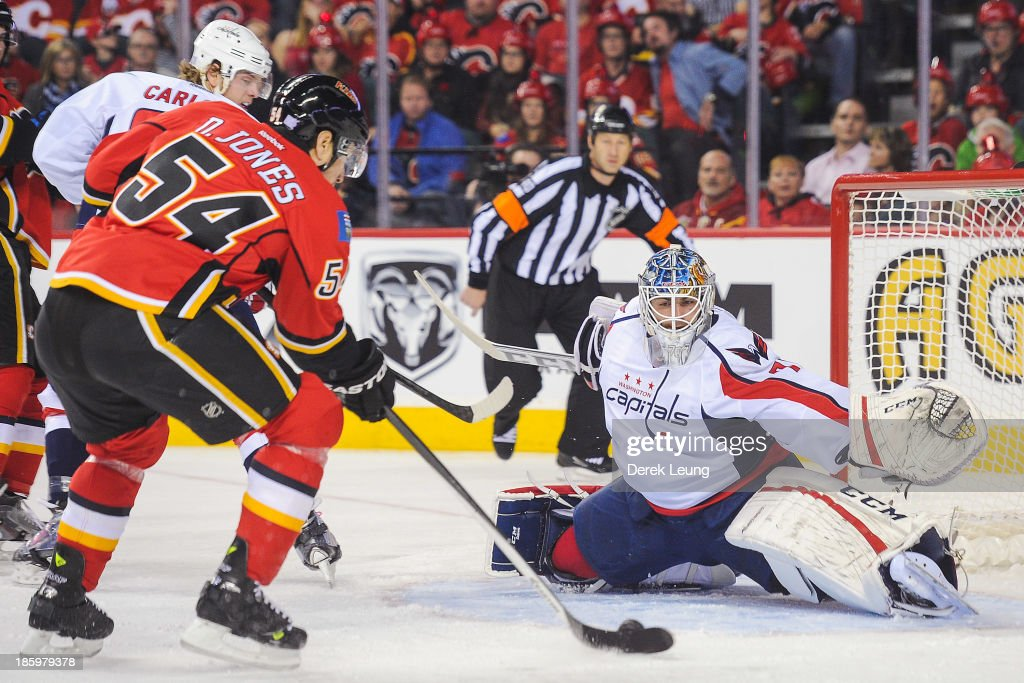 Braden Holtby #70 of the Washington Capitals stops the shot of David Jones #54 of the Calgary Flames during an NHL game at Scotiabank Saddledome on October 26, 2013 in Calgary, Alberta, Canada.