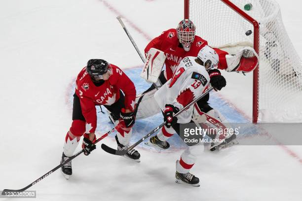 Braden Schneider and goaltender Devon Levi of Canada defend against Valentin Hofer of Switzerland during the 2021 IIHF World Junior Championship at...