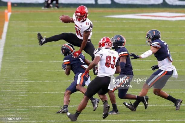 Braden Smith of the Louisville Cardinals hurdles over Nick Grant of the Virginia Cavaliers in the first half during a game at Scott Stadium on...
