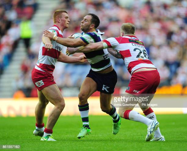 Bradford Bulls' Luke Gale is tackled by Wigan Warriors' Jack Hughes and Dom Crosby during the Super League match at the DW Stadium Wigan