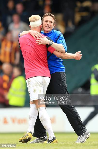 Bradford City manager Phil Parkinson celebrates with his player Andrew Davies on the pitch after the final whistle