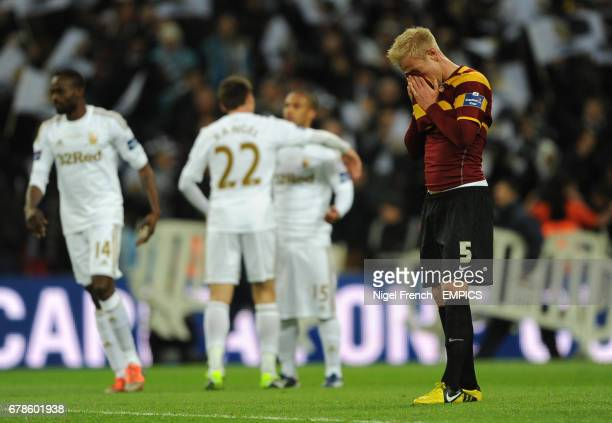 Bradford City's Andrew Davies shows dejection after the final whistle as Swansea City's players celebrate