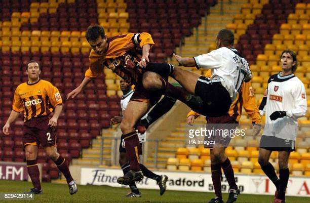 Bradford City's David Weatherall challenges Walsall's Julian Bennett for a high ball during the CocaCola League One match at Valley Parade Bradford...