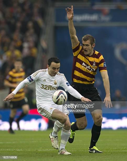 Bradford City's English striker James Hanson vies with Swansea City's English midfielder Leon Britton during the League Cup final football match...