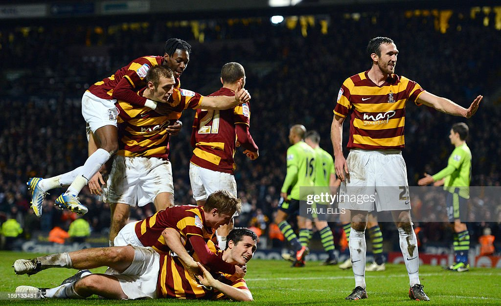 """Bradford City's Irish defender Carl McHugh (bottom) celebrates with teammates after scoring the third goal against Aston Villa during the English League Cup football match between Bradford City and Aston Villa at The Coral Windows Stadium in Bradford, England, on January 8, 2013. Bradford won the match 3-1. USE. No use with unauthorized audio, video, data, fixture lists, club/league logos or """"live"""" services. Online in-match use limited to 45 images, no video emulation. No use in betting, games or single club/league/player publications."""
