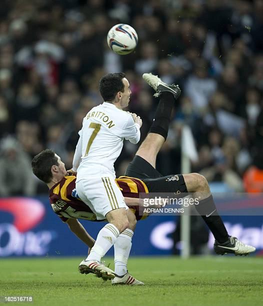 Bradford City's Irish defender Carl McHugh tries an overhead kick under pressure from Swansea City's English midfielder Leon Britton during the...