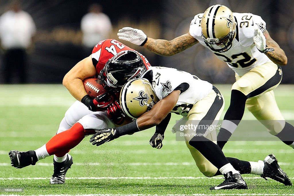 Bradie Ewing #34 of the Atlanta Falcons is brought down Jabari Greer #33 of the New Orleans Saints during a game at the Mercedes-Benz Superdome on September 8, 2013 in New Orleans, Louisiana.