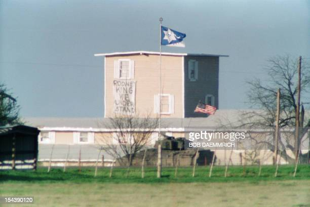 A Bradley armored personel carrier flies the US flag 31 March 1993 in Waco as it passes near the front of the branch Davidian compound during talks...