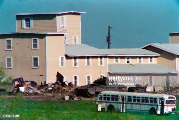 A Bradley armored personnel carrier pulls a trailer containing rolls of concertina wire on April 10 1993 past the front of the Branch Davidian...