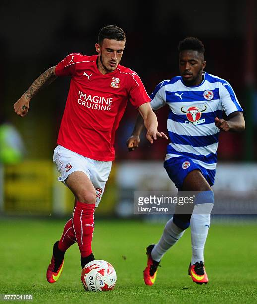 Bradley Barry of Swindon Town is tackled by Tariqe Fosu of Reading during the Pre Season Friendly match between Swindon Town and Reading at the...