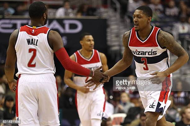 Bradley Beal and John Wall of the Washington Wizards celebrate a point against the Portland Trail Blazers during the first half at Verizon Center on...