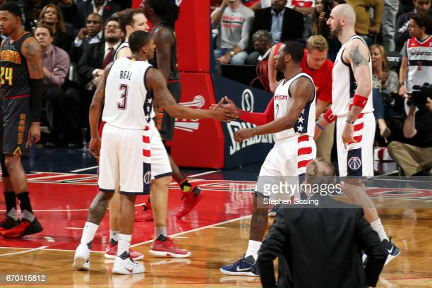 Bradley Beal and John Wall of the Washington Wizards high five each other during the game against the Atlanta Hawks during Game Two of the Eastern...