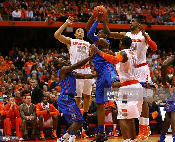 Bradley Beal of the Florida Gators shoots with the help of teammate Erving Walker against Brandon Triche Scoop Jardine and Fab Melo of the Syracuse...