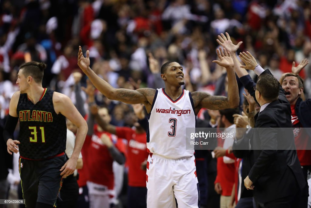 Bradley Beal #3 of the Washington Wizards celebrates with head coach Scott Brooks in front of Mike Muscala #31 of the Atlanta Hawks after hitting a three pointer in the second half of the Wizards 109-101 win in Game Two of the Eastern Conference Quarterfinals during the 2017 NBA Playoffs at Verizon Center on April 19, 2017 in Washington, DC.