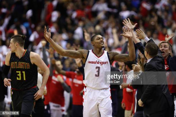Bradley Beal of the Washington Wizards celebrates with head coach Scott Brooks in front of Mike Muscala of the Atlanta Hawks after hitting a three...