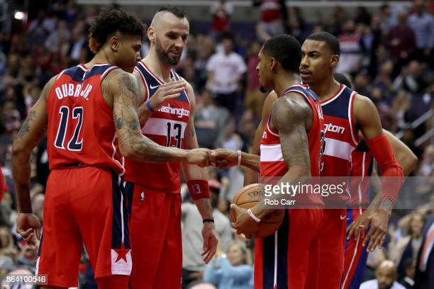 Bradley Beal of the Washington Wizards celebrates with Kelly Oubre Jr #12 Marcin Gortat and Otto Porter Jr #22 after scoring and getting fouled...