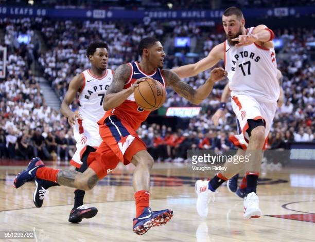 Bradley Beal of the Washington Wizards drives to the basket as Jonas Valanciunas of the Toronto Raptors defends during the first half of Game Five in...