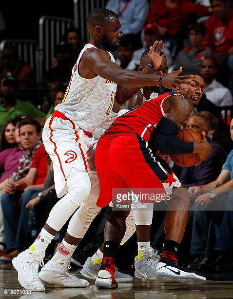 Bradley Beal of the Washington Wizards is trapped by Tim Hardaway Jr #10 and Paul Millsap of the Atlanta Hawks at Philips Arena on October 27 2016 in...
