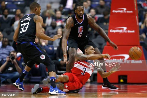 Bradley Beal of the Washington Wizards passes the ball in front of Wesley Johnson and DeAndre Jordan of the LA Clippers in the first half at Capital...