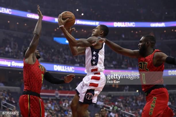 Bradley Beal of the Washington Wizards puts up a shot in front of Paul Millsap and Tim Hardaway Jr #10 of the Atlanta Hawks in the first half during...