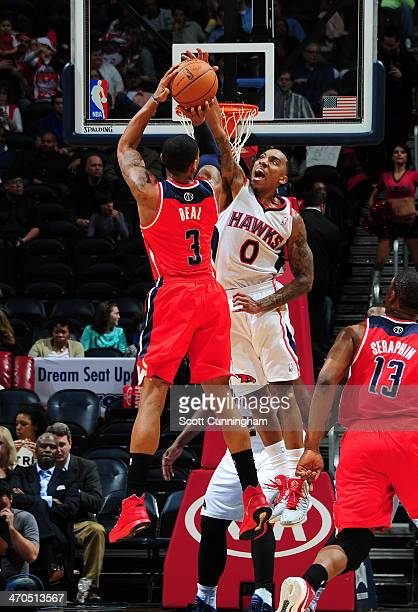 Bradley Beal of the Washington Wizards shoots against Jeff Teague of the Atlanta Hawks on February 19 2014 at Philips Arena in Atlanta Georgia NOTE...