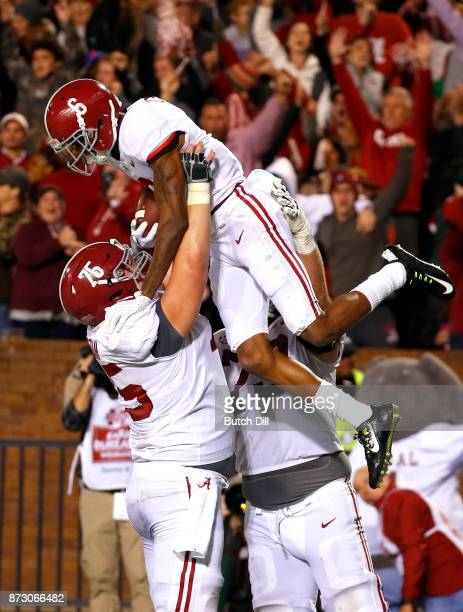 Bradley Bozeman of the Alabama Crimson Tide celebrates as he holds up DeVonta Smith after he scored the winning touchdown to defeat the Mississippi...