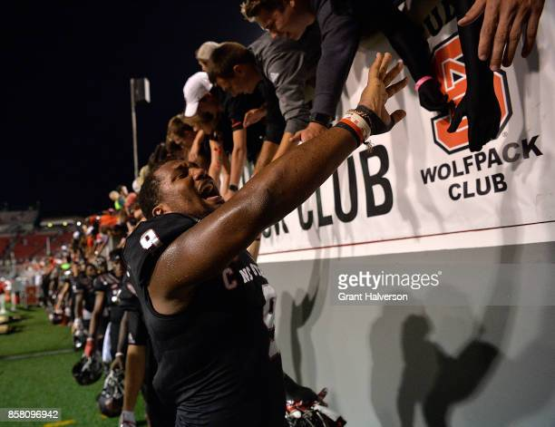 Bradley Chubb of the North Carolina State Wolfpack celebrates with fans after a win against the Louisville Cardinals during the game at Carter Finley...