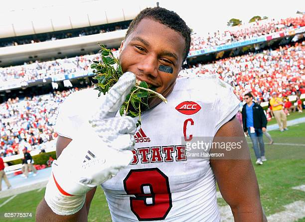Bradley Chubb of the North Carolina State Wolfpack leaves the field with a piece of the Kenan Stadium hedges between his teeth following a win...