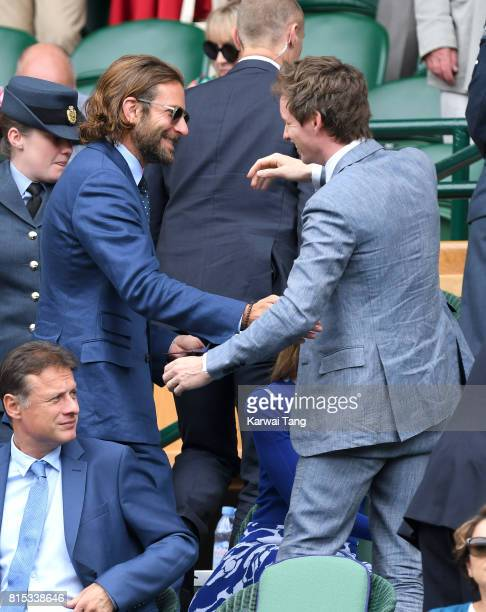 Bradley Cooper and Eddie Redmayne greet each other as they attend day 13 of Wimbledon 2017 on July 16 2017 in London England