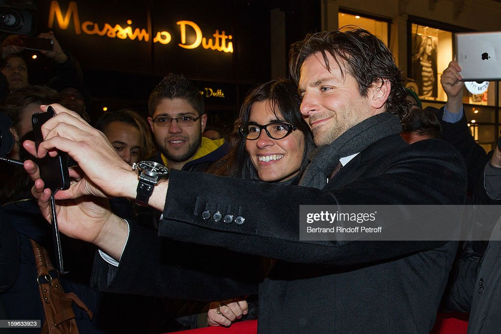 Bradley Cooper (R) takes a photo of himself and a fan with a fan's mobile phone while attending the premiere of 'Happiness Therapy' (Silver Linings Playbook) at Cinema UGC Normandie on January 17, 2013 in Paris, France.