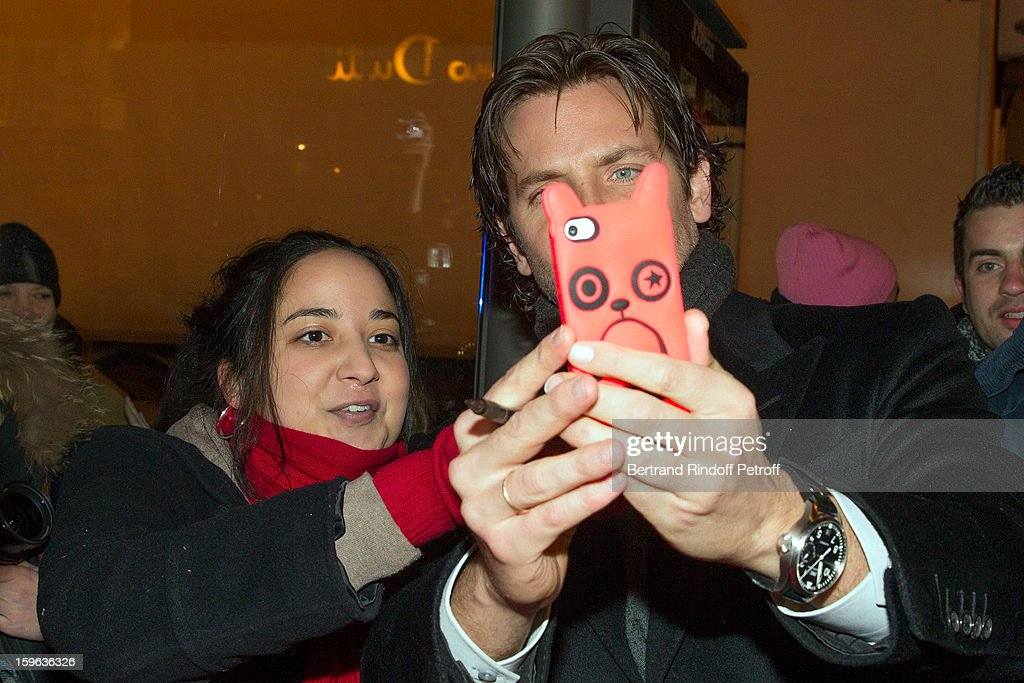 Bradley Cooper (R) takes a photo of himself with a fan using a fan's mobile phone while arriving to the premiere of 'Happiness Therapy' (Silver Linings Playbook) at Cinema UGC Normandie on January 17, 2013 in Paris, France.