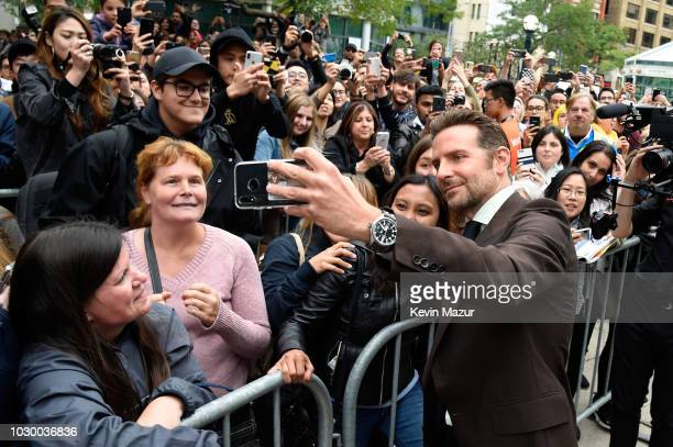 Bradley Cooper takes selfies with fans as he attends the A Star Is Born premiere during 2018 Toronto International Film Festival at Roy Thomson Hall...