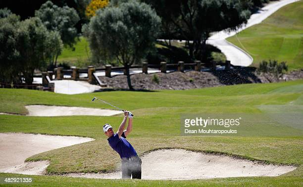 Bradley Dredge of Wales hits his second shot on the 5th hole out of the bunker during day three of the NH Collection Open held at La Reserva de...