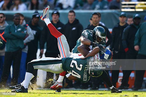 Bradley Fletcher and Nate Allen of the Philadelphia Eagles tackles Victor Cruz of the New York Giants at Lincoln Financial Field on October 27, 2013...