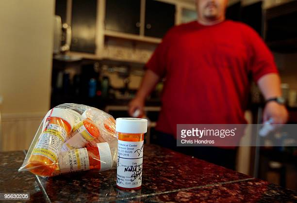 Bradley Hammond walks in his kitchen near some of the many prescription drugs he has been prescribed by doctors to help him cope with his PTSD...