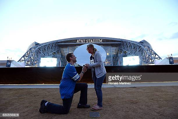 Bradley Herzog gets on one knee to propose marriage to Tabitha Lannet of Battle Creek Michigan outside of ATT Stadium before a game between the...